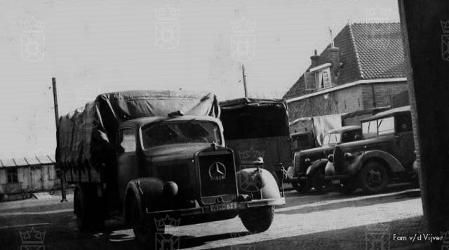 De hoofdingang van de veiling, rechts op de achtergrond zijn de houten barakken te zien.