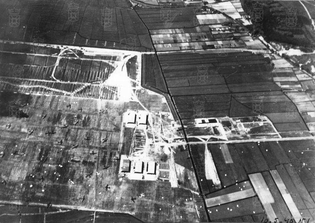 Op deze luchtfoto, gemaakt tijdens de Duitse inval op 10 mei 1940, zijn de drainagesleuven aan de zuidkant van het vliegveld goed te zien. Het vliegveld ligt bezaaid met parachutes en Ju52 transportvliegtuigen.