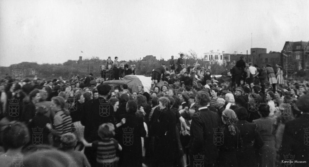Een uitzinnige menigte beklimt de wagens van de RAF die bij de Duinoord aangekomen zijn.