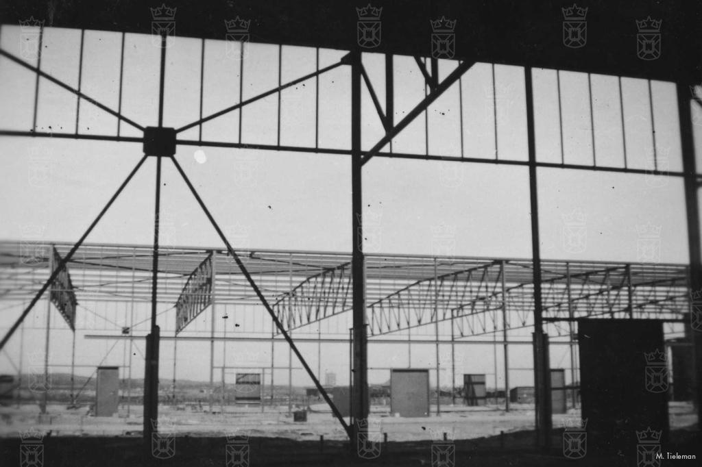 De bouw van de hangaars. Het geraamte is reeds opgetrokken en de deuren zijn geplaatst. Nu de beplating nog.