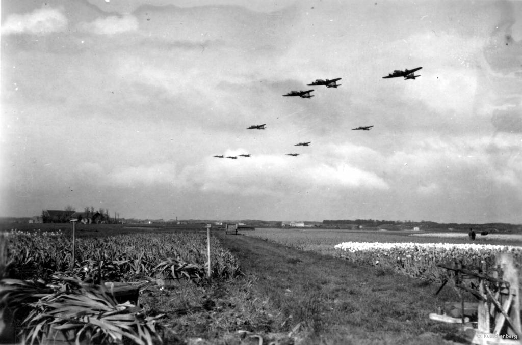 Geallieerde vliegtuigen vliegen laag boven het vliegveld tijdens een voedseldropping op 1 mei 1945.