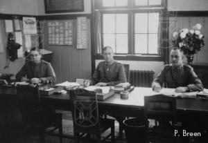 Enkele militairen van de staf houden kantoor in de veiling Flora.