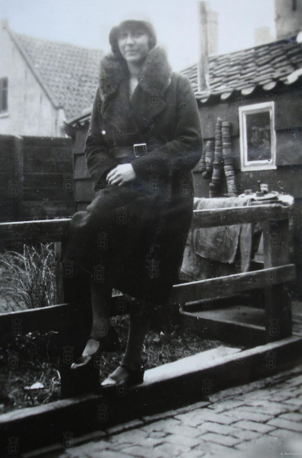 Marijtje van der Plas, met op de achtergrond de drie huizen van vader Teun van der Plas.